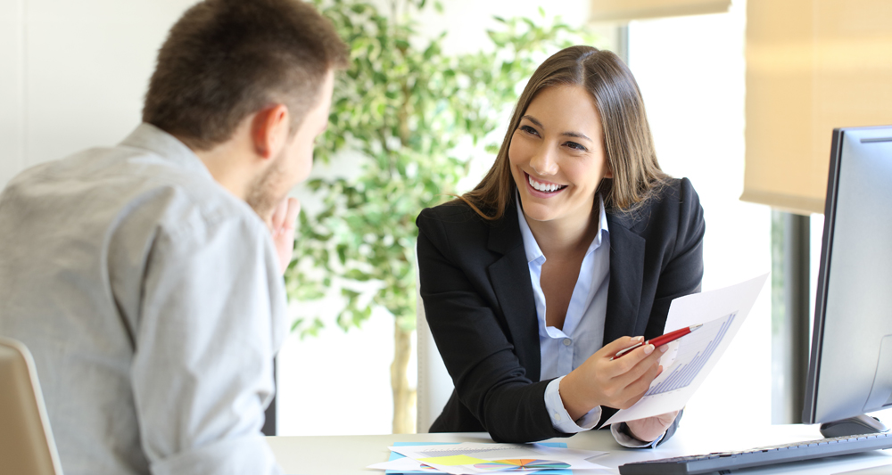 woman smiling pointing at paper of financial figures feedback