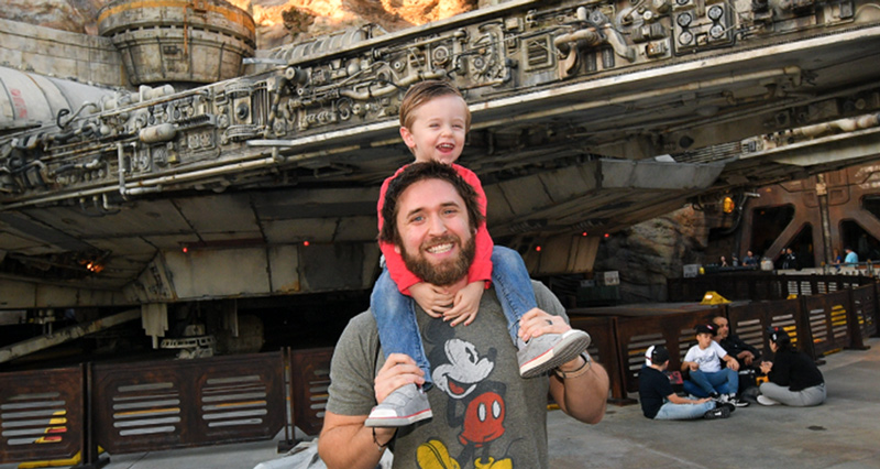 employee chad smiling with son at disney world in front of millenium falcon